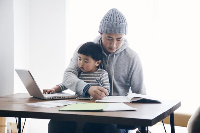 Japanese man in casual clothes writing a document and his son using a laptop on the desk.