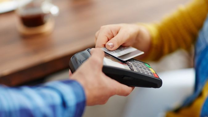 Close-up of unrecognizable customer choosing contactless payment using credit card while waitress accepting payment over nfc technology.