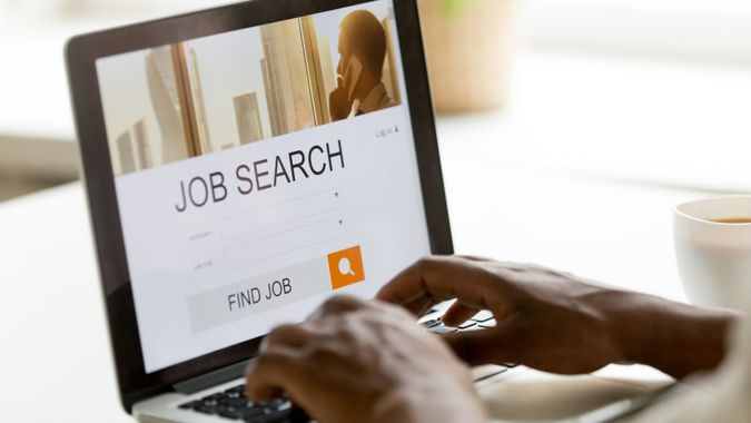 African man browsing work opportunities online using job search computer app, black jobless seeker looking for new vacancies on website page at laptop screen, recruitment concept, rear close up view.