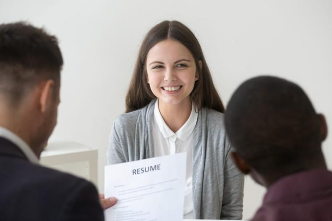 Happy smiling millennial applicant being interviewed by diverse hr managers, recruiting team reading resume of positive funny graduate girl looking for first job, good impression and hiring concept.