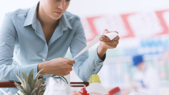 Woman shopping at the supermarket, she is checking a long grocery receipt and leaning on a cart, budgeting and lifestyle concept.