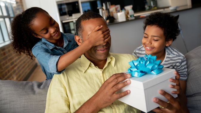 Kids surprising their father with a gift for Father's Day stock photo