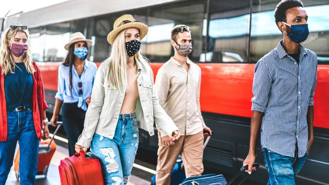 Multiracial friends group walking at railway station platform, staying safe while traveling