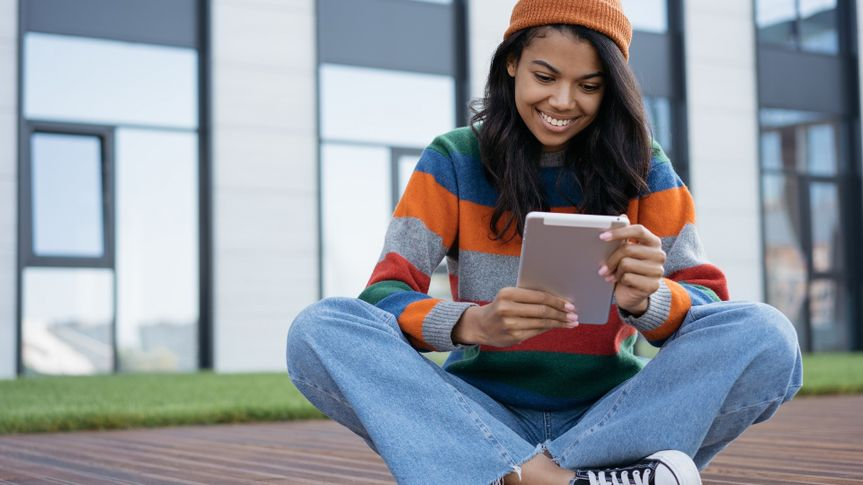 Student studying, learning language, online education concept. Beautiful African American woman using digital tablet, watching movie outdoors stock photo