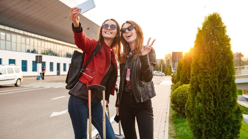 Image of two young caucasian women wearing sunglasses taking selfie photo on smartphone, while standing with luggage near airport waiting for flight or after departure. Air travel concept stock photo