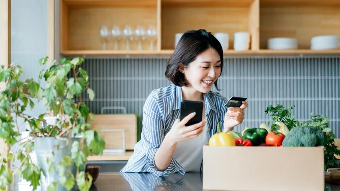 Beautiful smiling young Asian woman grocery shopping online with mobile app device on smartphone and making online payment with her credit card, with a box of colourful and fresh organic groceries on the kitchen counter at home stock photo