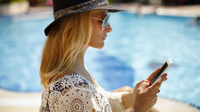 Attractive woman texting by the swimming pool stock photo