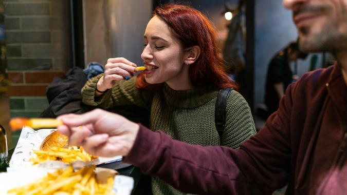 Hungry couple in fast food restaurant stock photo