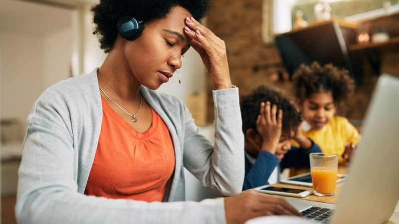 Black single mother feeling frustrated while working at home. stock photo