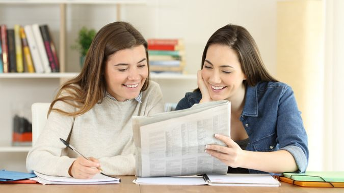 Two happy students talking about newspaper news at home.