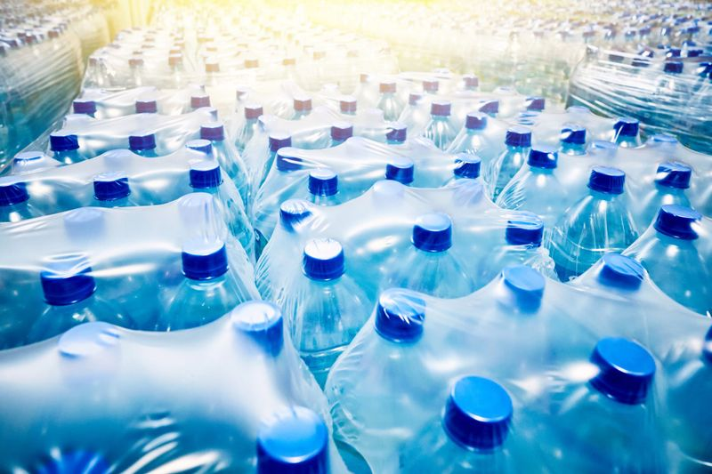 Many packaged blue mineral water bottles in stock in a store or market.