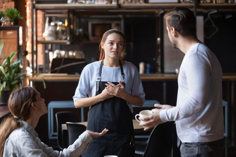 Hostile angry restaurant client couple or friends talking with waiting staff in public place complains about cold coffee long service, spoiled tasteless dish waitress feels guilty mixed orders concept.