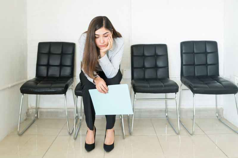 Bored Hispanic female applicant sitting with resume in waiting room during recruitment at office.