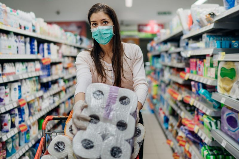 Woman shopper with mask and gloves panic buying and hoarding toilette paper in supply store.