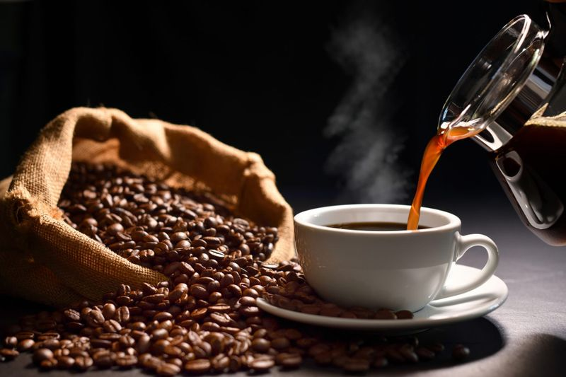 Pouring coffee with smoke on a cup and coffee beans on burlap sack on black background.