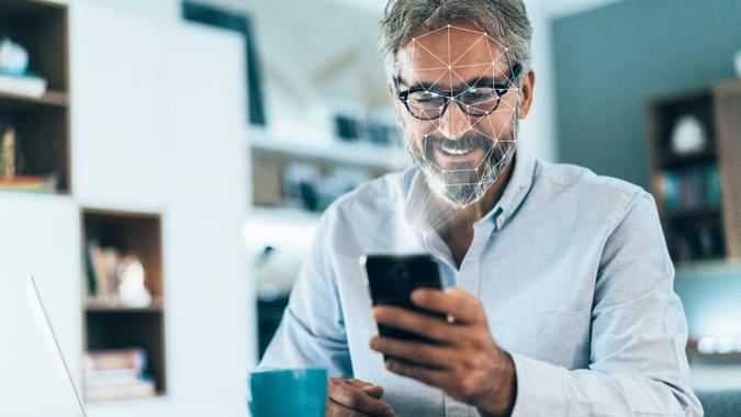 Facial recognition software scans the face of elegant senior man holding smart phone at home.
