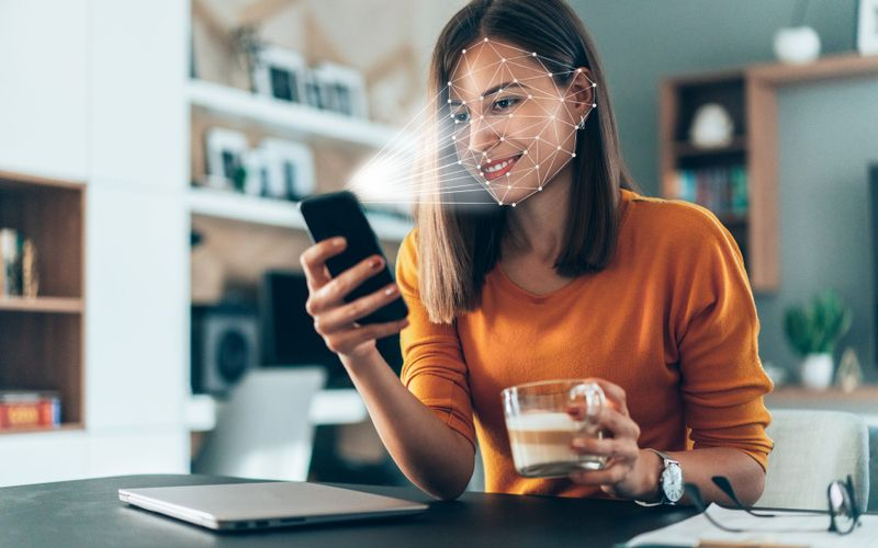 Facial recognition software scans the face of young woman holding smart phone at home.
