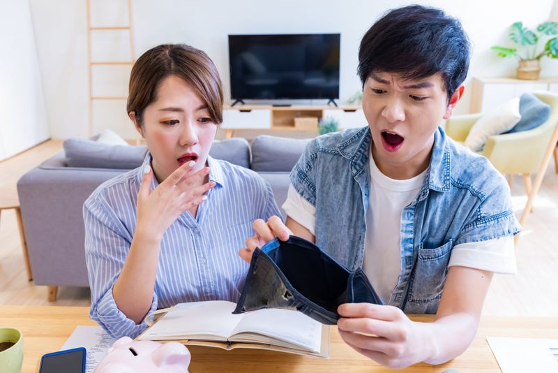 Asian couple blow their money with empty wallet and feel shocked.