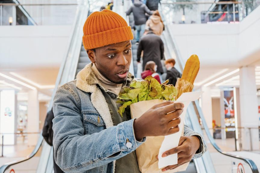 African man with a paper bag of groceries looks surprised and upset at a receipt from a supermarket with high prices against the background of an escalator with customers in the shopping center.