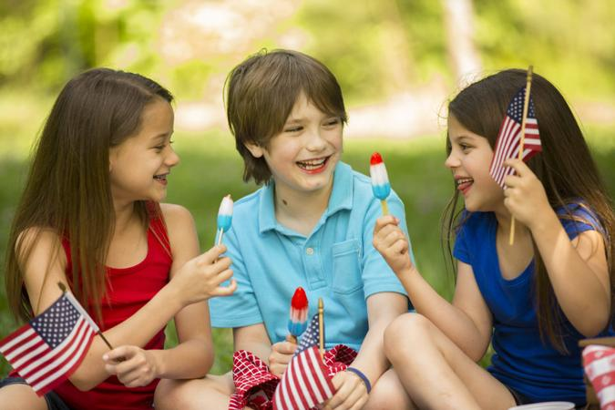 Three American children enjoy a summer picnic outdoors to celebrate USA's Memorial Day, Independence Day, or Labor Day holiday.