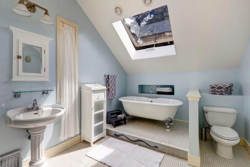 Light blue velux bathroom with window.