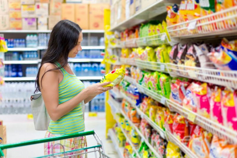 Woman buys potato chips in the store.