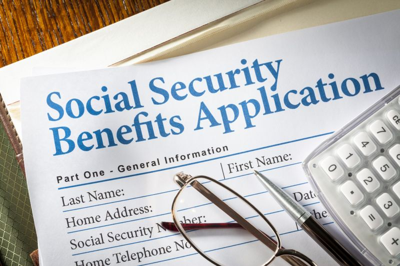 Social Security Benefits form with pen, glasses, and calculator.