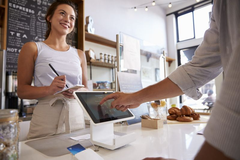 Customer using touch screen to make payment at a coffee shop.