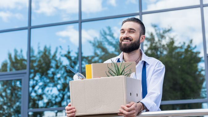 happy businessman with cardboard box with office supplies in hands standing outside office building, quitting job concept.