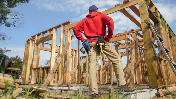 Roofer ,carpenter working on roof structure at construction site stock photo