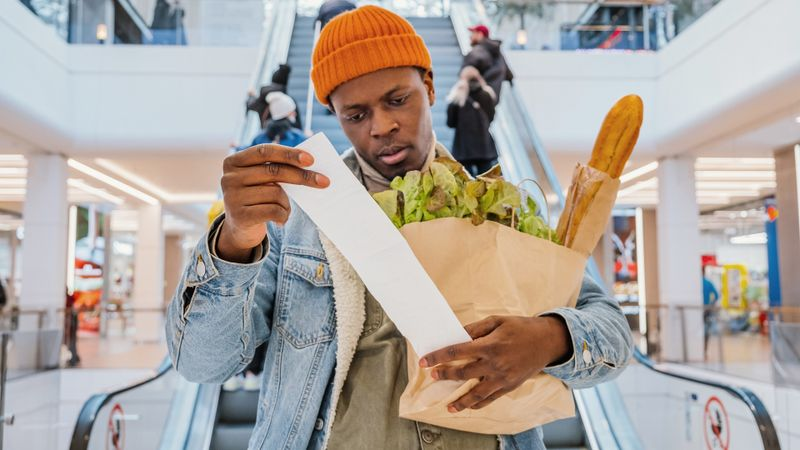 Surprised black man looks at receipt total with food in mall stock photo
