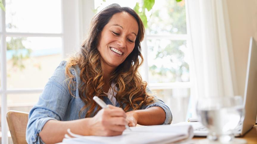 Smiling mature woman writing in a notebook while working from home stock photo
