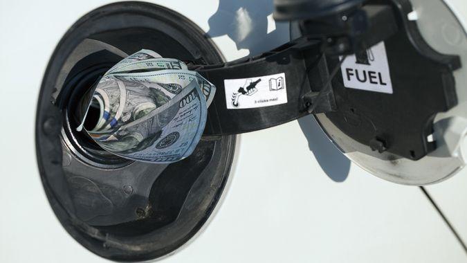 Gas Prices Concept: Gas tank eats money stock photo