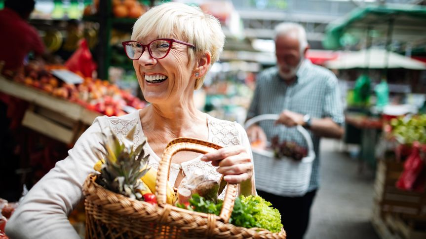 Senior couple buying fresh vegetables at the local market.