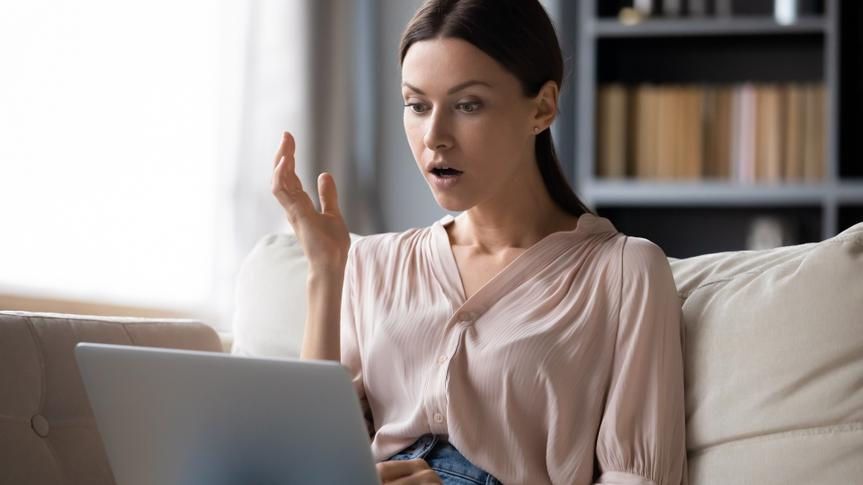 Shocked young woman looking at laptop screen, unexpected news stock photo