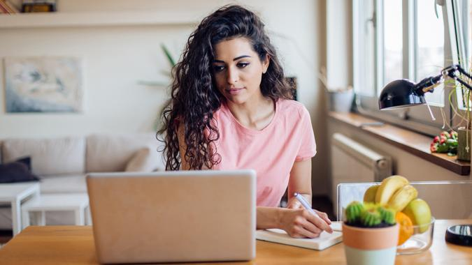 Unemployed young woman searching for a job online.