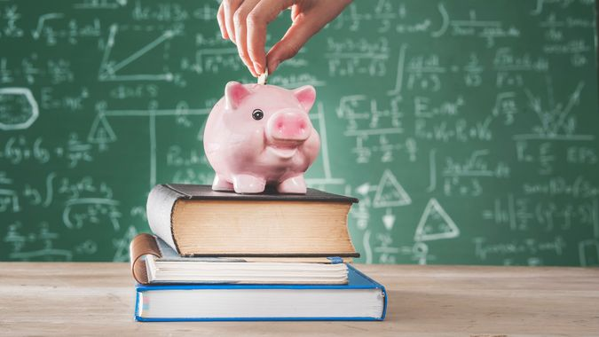 Female putting coin into piggy bank.