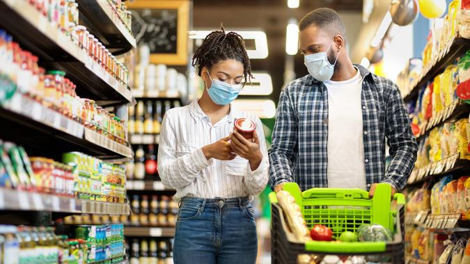 African Family Couple In Shop Buying Groceries Wearing Face Mask Choosing Food Goods Walking With Shopping Cart In Supermarket Store.