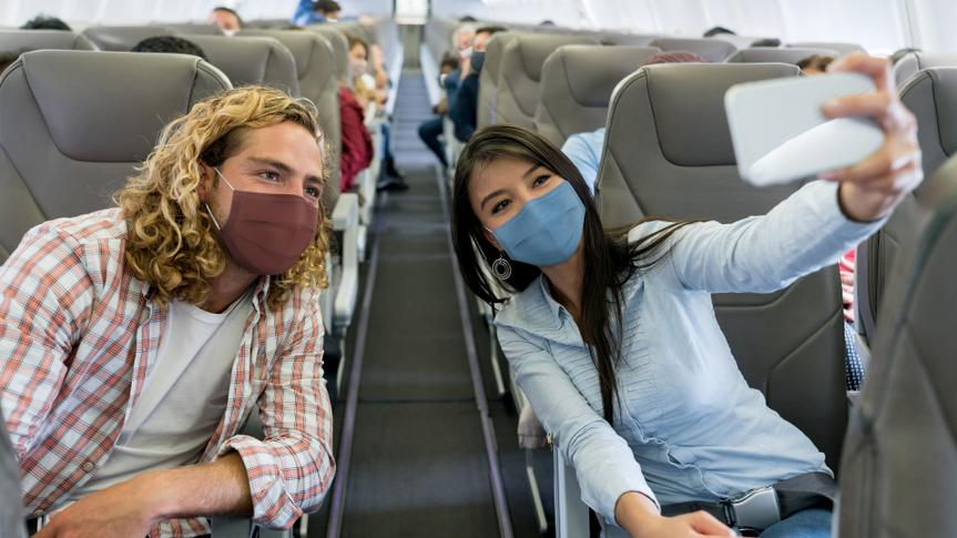 Friends traveling by plane wearing facemasks and taking a selfie stock photo
