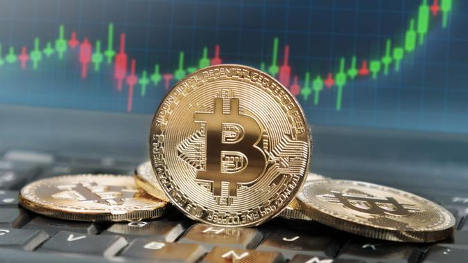 Bitcoins on keyboard with screen in the background displaying rising trend of its value.