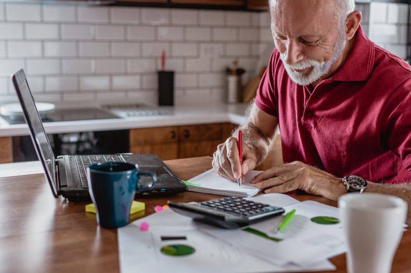 Senior man is sitting at the table, using a lpatop and planning home budget and writing something on the paper.
