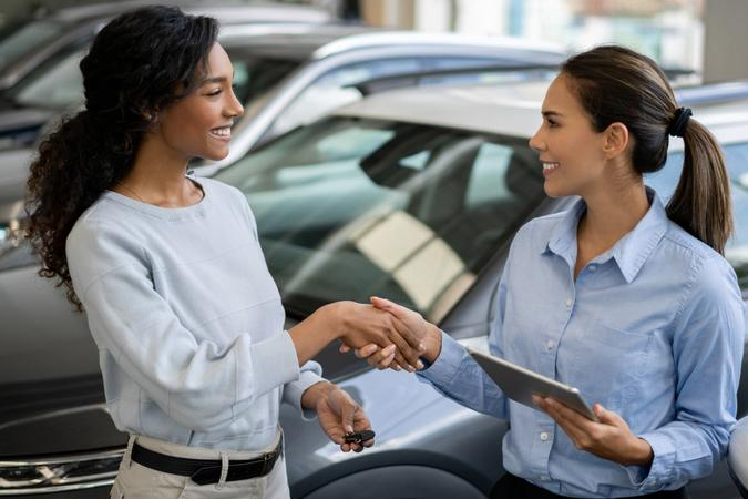 Happy woman buying a car and closing the deal with a handshake with the saleswoman at the dealership.