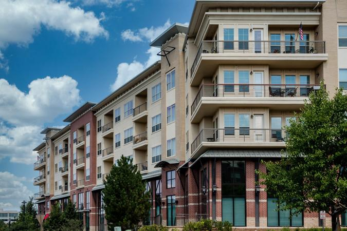 Modern brick and stucco condo buildings with balconies and garages.