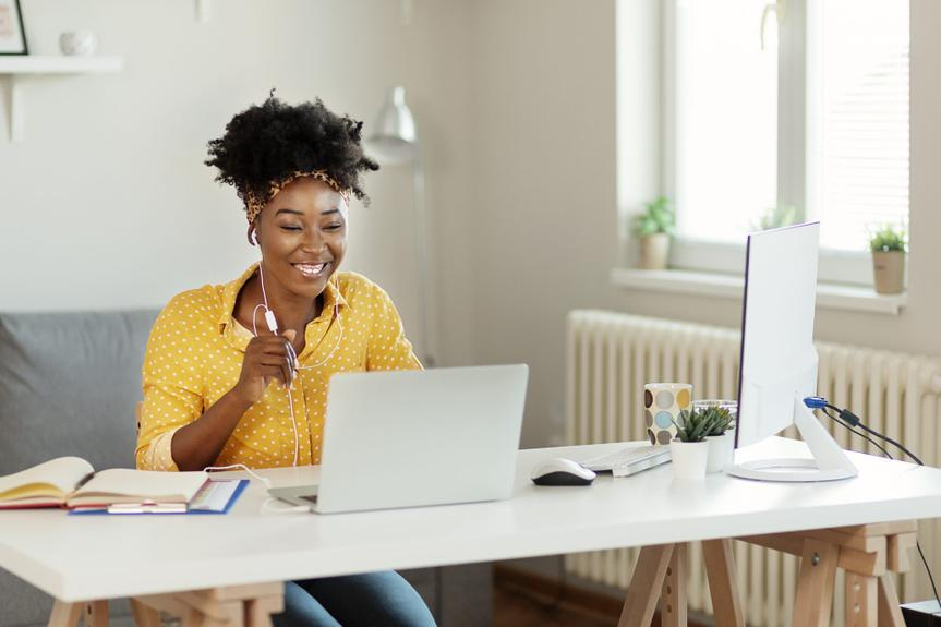 Happy African American Businesswoman Wearing Headphones, Looking at Laptop Screen, Holding Pleasant Conversation With Partners Clients Online, Working Remotely at Workplace.