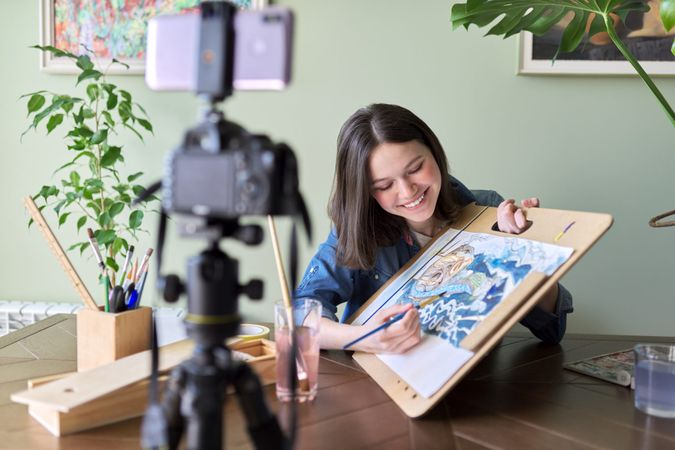 Artist, teenage girl, draws records on video camera for blog.