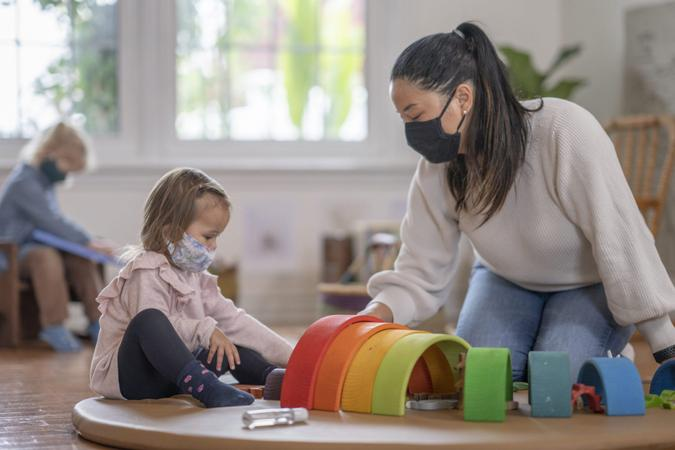 Young girl playing on a play mat at daycare while wearing a mask due to COVID-19.
