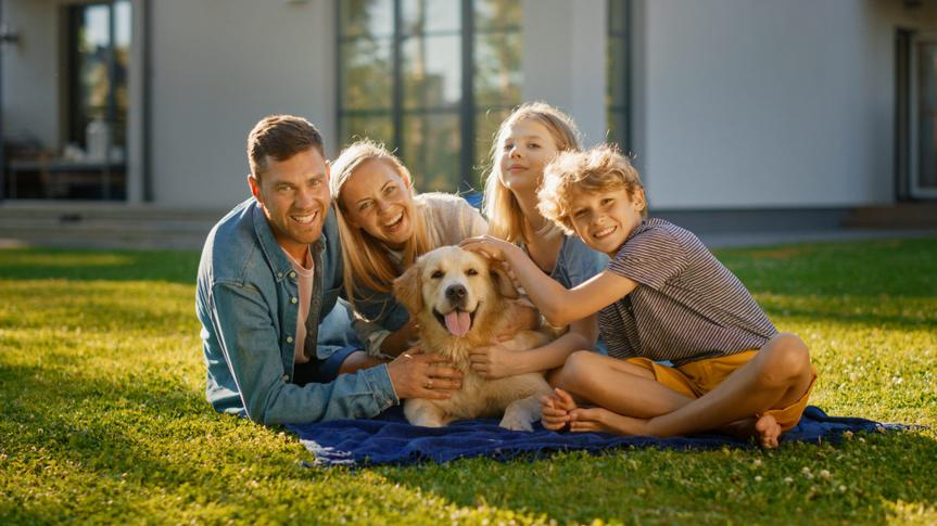 Portrait of Father, Mother and Son Having Picnic on the Lawn, Posing with Happy Golden Retriever Dog.
