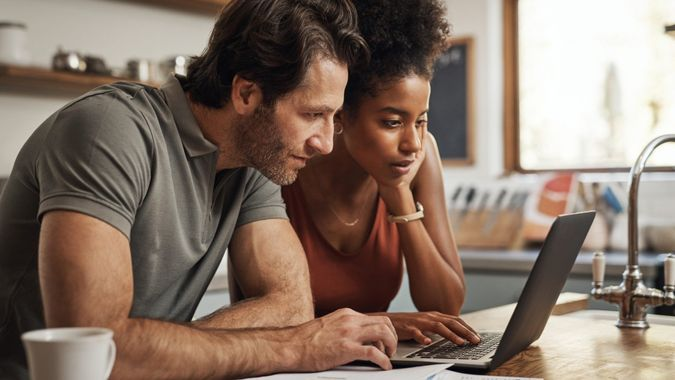 Cropped shot of a couple using their laptop and going through paperwork at home.