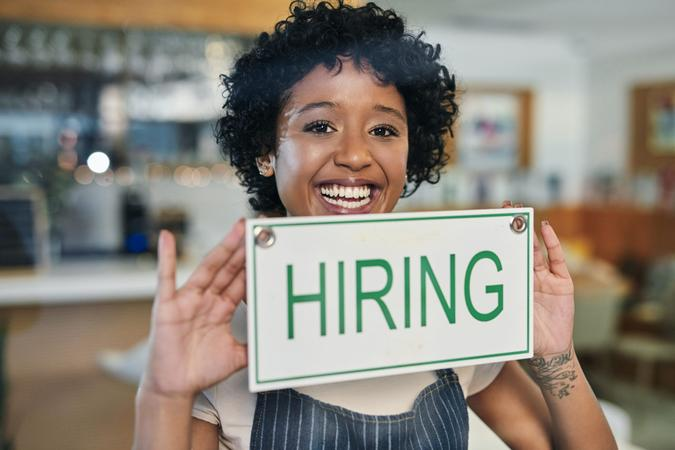 """Portrait of a young woman holding a """"hiring"""" sign in her store."""
