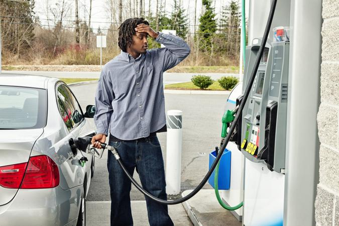 """""""Photo of a young man watching filling his gas tank, watching in disbelief as the dollar amount climbs on the gas pump display too quickly to comprehend."""